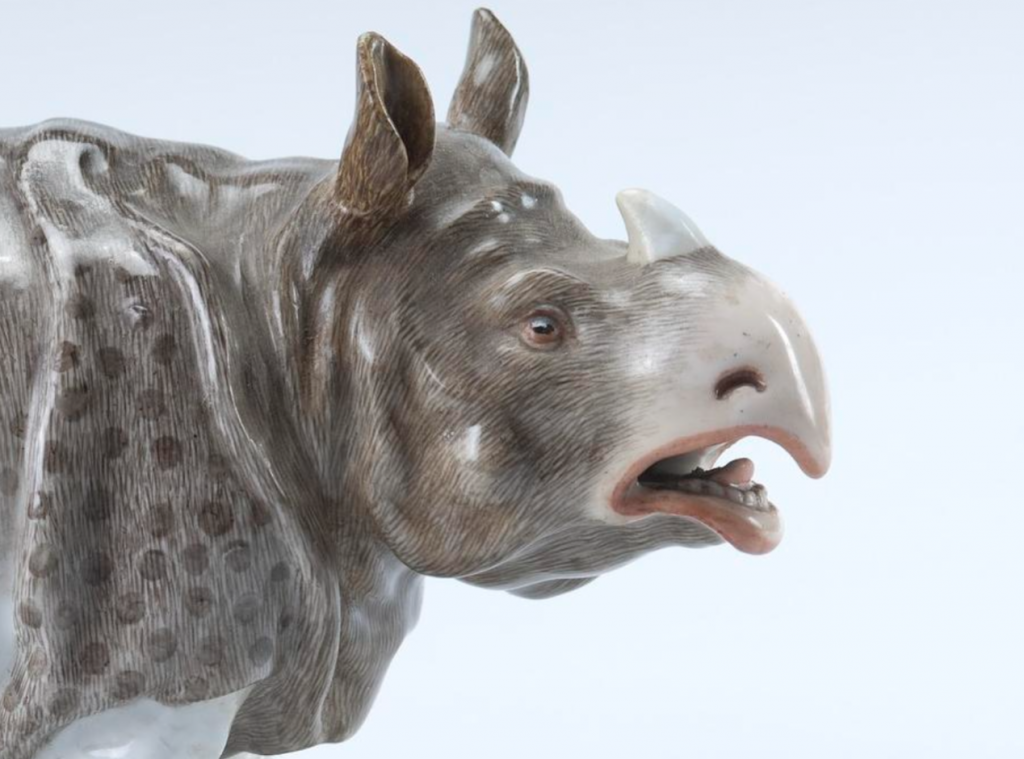 porcelain rhinoceros figurine, looking right, head and shoulders, realistically painting in speckled gray and white, mouth slightly open.
